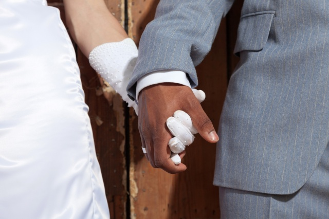 Closeup of holding hands of stylish wedding couple. Mixed race.